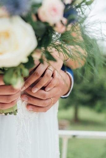 Main des mariés avec leurs alliances et le bouquet