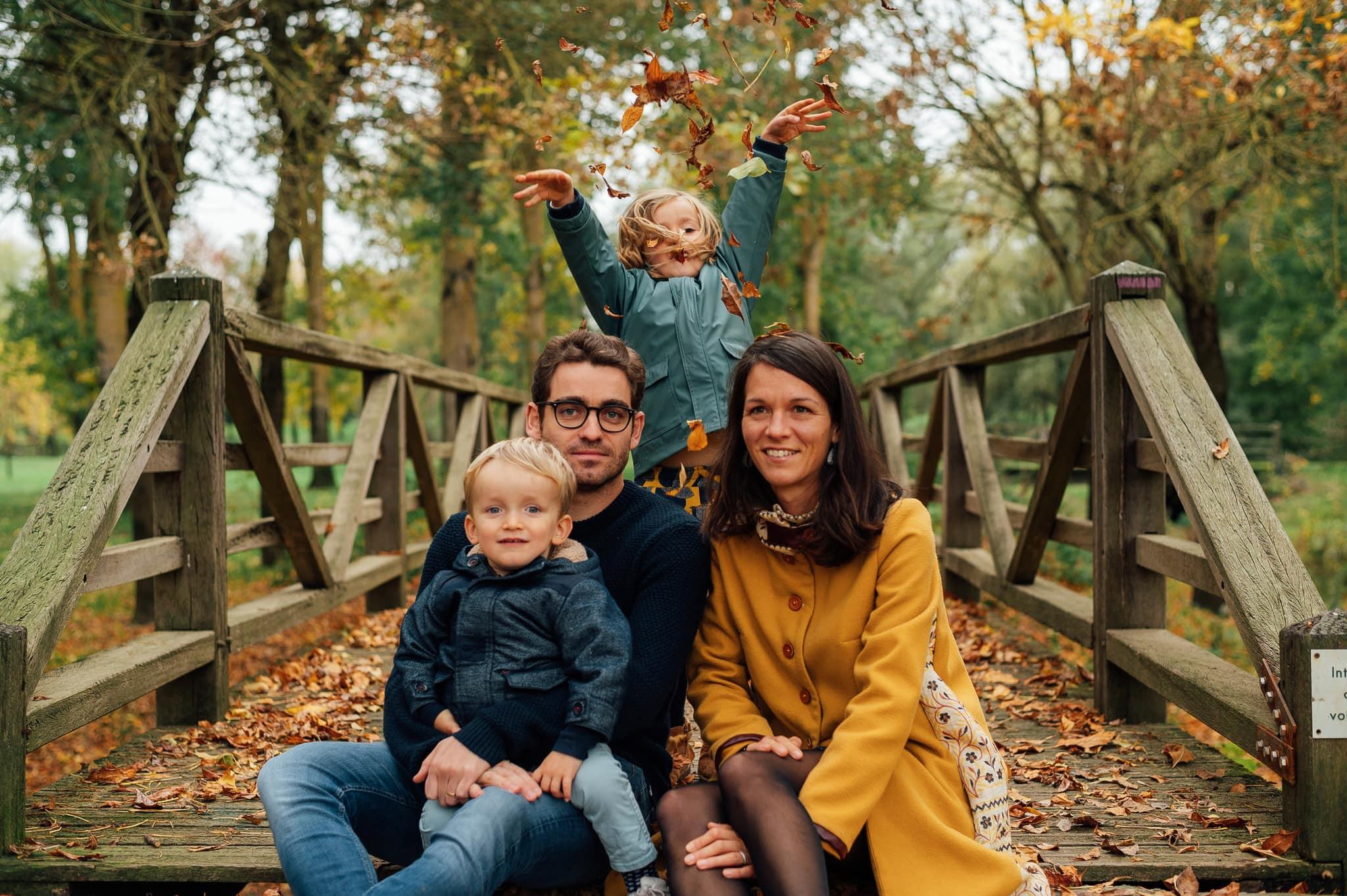 Famille joue dans les feuilles de l'automne